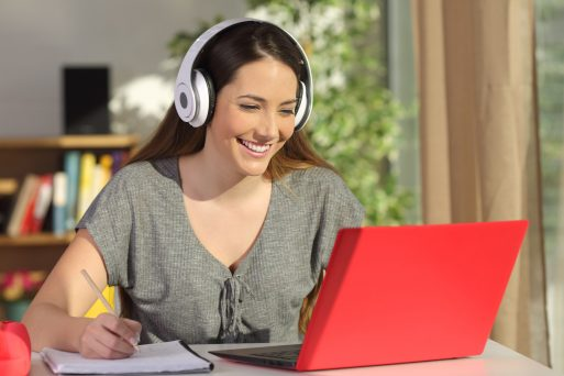 stock-photo-beautiful-portrait-of-a-student-learning-on-line-watching-video-tutorials-with-a-red-laptop-and-561927853
